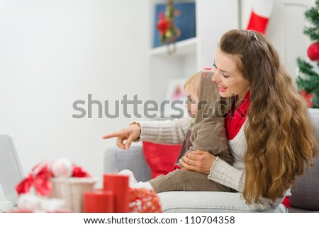 Happy young mother spending Christmas with baby and pointing on laptop - stock photo