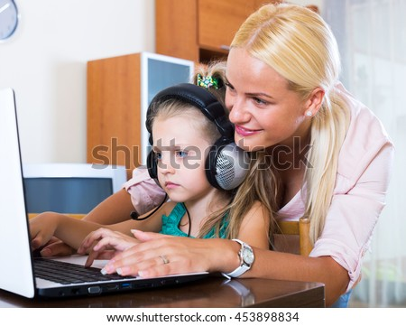 Happy young mother teaching little daughter to use laptop