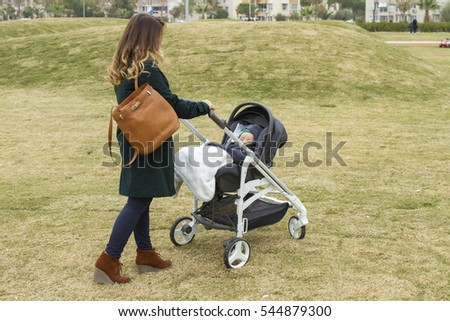 Happy young mother walking with baby stroller outdoors on the nature