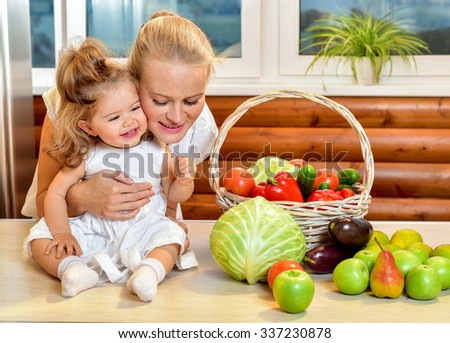 Happy young mother with a baby in the kitchen interior. Fresh vegetables and fruits. - stock photo