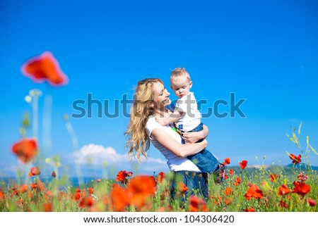 Happy young mother with a child in a poppy field - stock photo