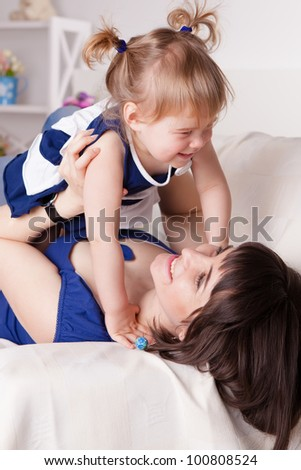 Happy young mother with a cute daughter having fun at home