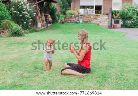 Happy young mother with baby in garden