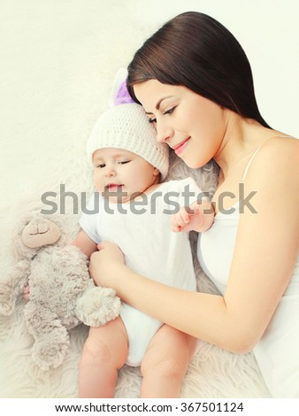 Happy young mother with baby together on bed at home, top view