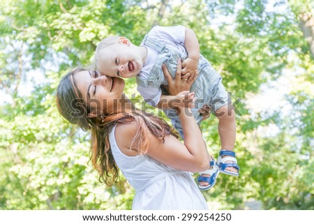 happy young mother with child - baby boy - outdoor portrait on green natural background - stock photo