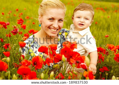 Happy young mother with children resting outdoors in poppies field - stock photo