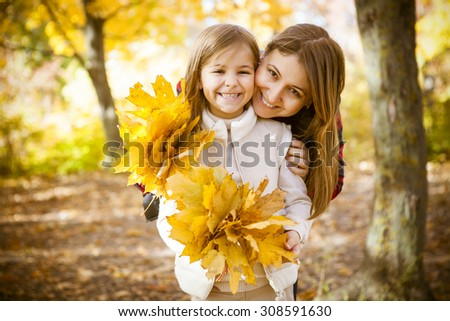 Happy young mother with daughter in autumn park - stock photo