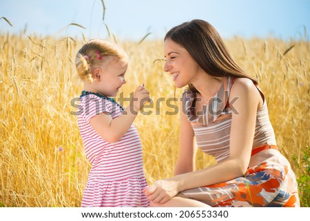 Happy young mother with daughter playing in wheat field - stock photo