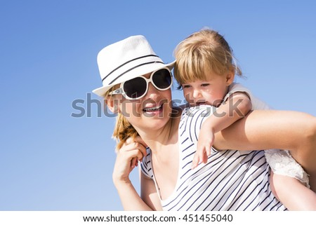 Happy young mother with hat and sunglasses holding daughter, smiling together.  Happy family concept