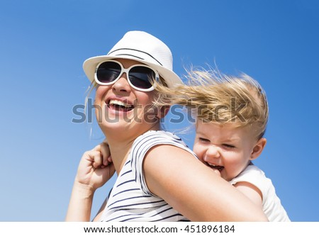 Happy young mother with hat and sunglasses holding daughter, smiling together. Happy family concept. Focus on child