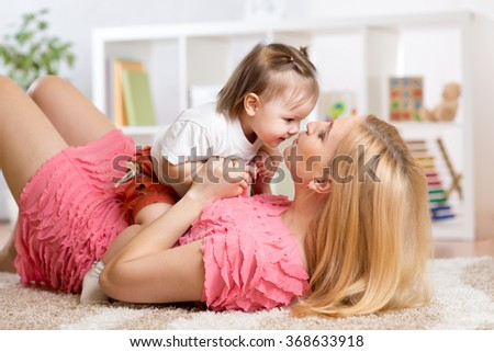 Happy young mother with her baby having fun pastime on the carpet in nursery - stock photo
