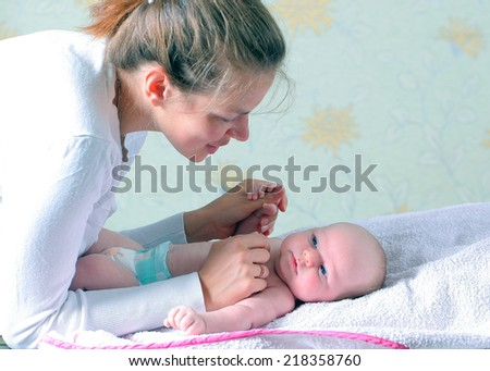 happy young mother with her baby in bed at home - stock photo