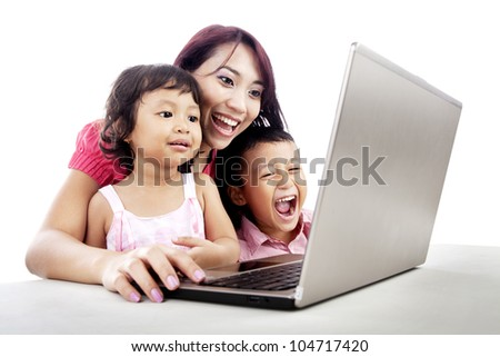 Happy young mother with her children using ultrabook laptop computer - stock photo