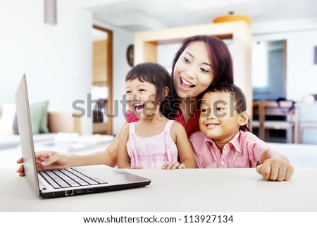 Happy young mother with her children using ultrabook laptop computer in their house - stock photo