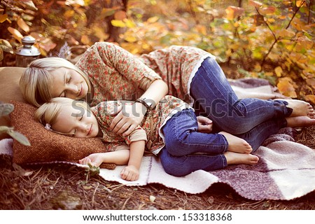 happy young mother with her cute little daughter outdoors in the park in Autumn