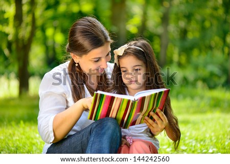 Happy young mother with her daughter at park - stock photo