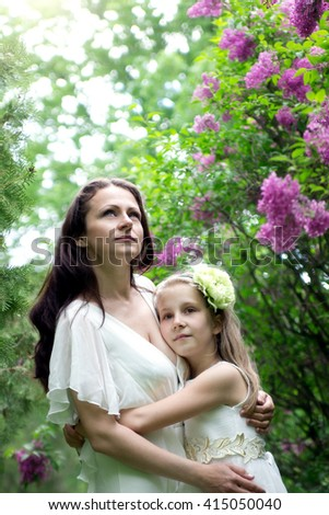 Happy young mother with her daughter in the garden. - stock photo