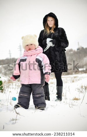 happy young mother with her daughter walking outdoors on a winter day - stock photo