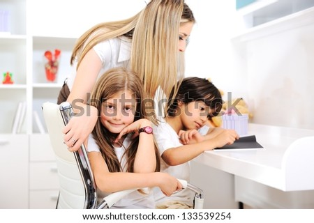 Happy young mother with her kids at children room - stock photo