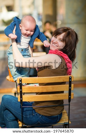 Happy young mother with her little son in a street cafe