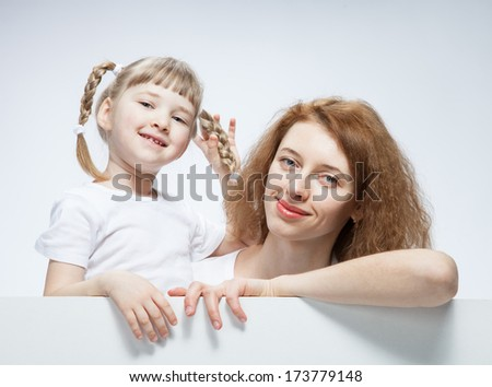 Happy young mother with her smiling daughter, neutral background - stock photo