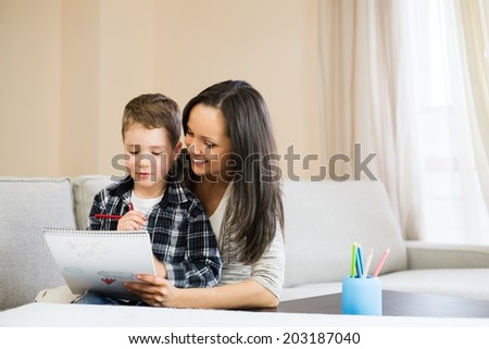Happy young mother with her son drawing in home interior  - stock photo
