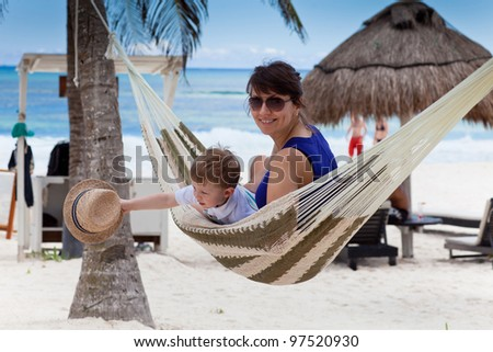 Happy young mother with her son in a hammock on a caribbean beach - stock photo