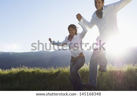 Happy young multiethnic couple jumping while holding hands in park - stock photo