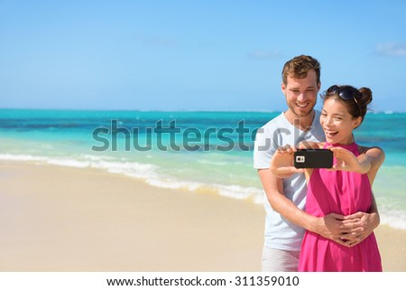 Happy young multiethnic couple taking selfie on mobile phone at beach. Loving partners are standing together while clicking pictures. Tourists are enjoying together at beach.