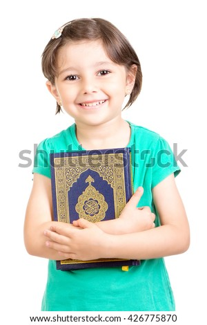 Happy young Muslim girl holding Quraan (Holy book) - Ready for Ramadan - stock photo