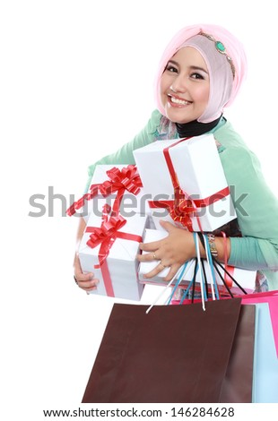 Happy young muslim woman with shopping bag and gift boxes isolated over white background - stock photo