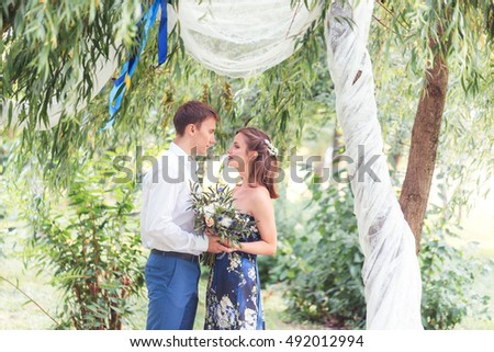 Happy young newlywed couple man holding hand and look his wife  in park. Holding a bouquet. Romantic.