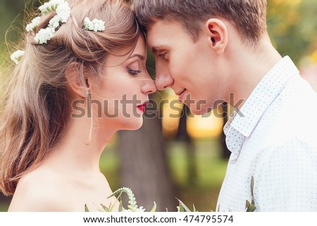 Happy young newlywed couple touching foreheads and noses in park. Romantic