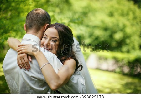 Happy young newlyweds hugging in the park