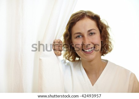 Happy young nurse pulling white curtain aside
