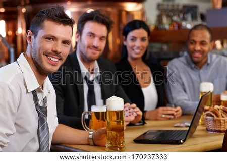 Happy young office worker drinking beer at pub with colleagues, holding mug, smiling.