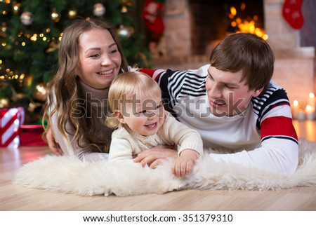 Happy young parents and child have a fun near Christmas tree at home.  Father, mother and son celebrating New Year together