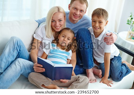 Happy young parents and their children reading book at home - stock photo