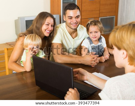 Happy young parents and two daughters sitting in front of social worker - stock photo