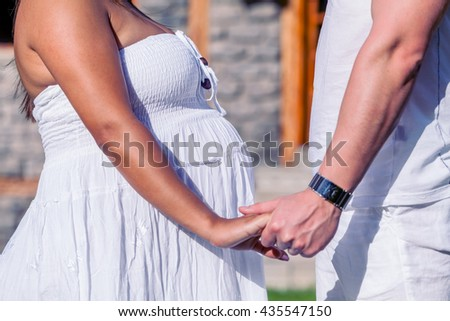 Happy Young Parents Expecting A Baby, Pregnant Woman With Husband Holding Hands In Nature  - stock photo