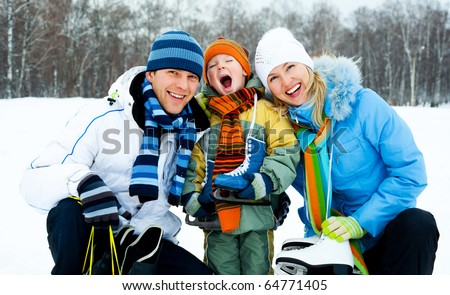 happy young parents going ice skating with their son - stock photo