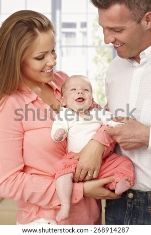 Happy young parents holding happy baby.
