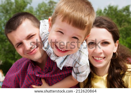 Happy young parents holding their son on a summer day - stock photo