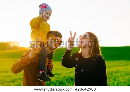Happy young parents playing and laughing with his young son in the summer at sunset. Concept of family - stock photo