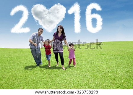 Happy young parents running with their children on the meadow under cloud shaped numbers 2016