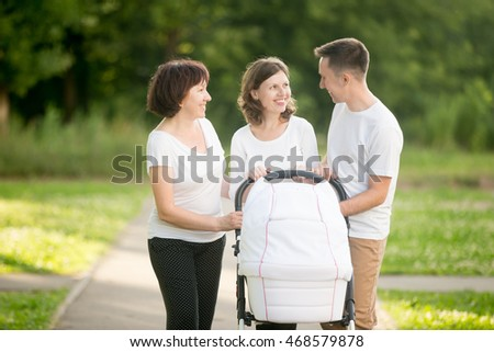 Happy young parents standing in park with new-born baby in pram talking and smiling, looking at each other. Happy grandmother looking at them standing nearby and smiling. Happy family concept