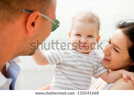 Happy young parents with child against the sea - stock photo