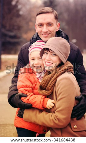 Happy young parents with   daughter  walking in   park in autumn.  - stock photo