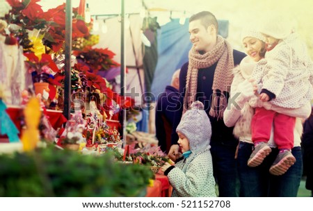 Happy young parents with little girls at counter with Poinsettia. Shallow focus