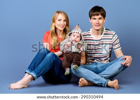 Happy young parents with their adorable baby. Family concept. Studio shot. - stock photo